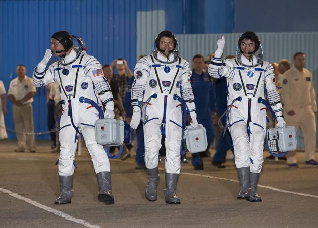 RUS05. BAIKNONUR (KAZAJISTÁN ), 22/07/2015.- El astronauta de la NASA Kjell Lindgren (i), el astronauta japonés Kimiya Yui (d) y el cosmonauta ruso Oleg Kononenko (c), miembros de la tripulación 44/45 son vistos hoy, miércoles 22 de julio de 2015, durante la ceremonia antes del despegue del cohete Soyuz TMA-17M de la Estación Espacial ISS en Baikonur (Kazajistán). EFE/SHAMIL ZHUMATOV/POOL