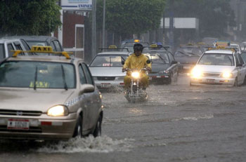 A man rides his motorcycle through a flooded street due to heavy rain in Managua October 6, 2008. Authorities in Nicaragua declared a state of alert along the country���s Pacific coast after days of heavy rain. REUTERS/Oswaldo Rivas (NICARAGUA)