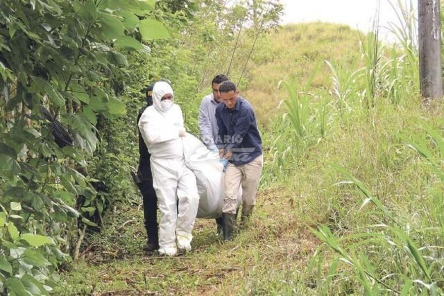 Forenses retiran los cuerpos en la escena del crimen. Foto cortesía de Diario Extra