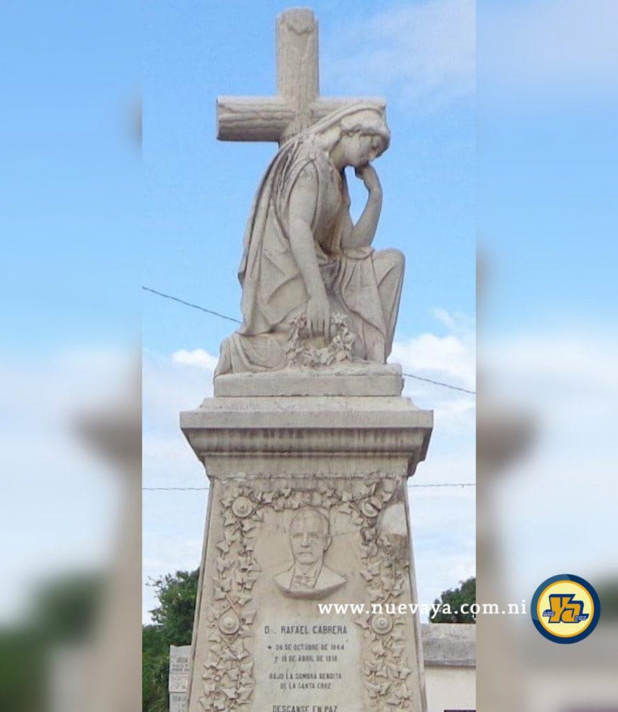 Escultura de una dama entristecida delante de una cruz de madera